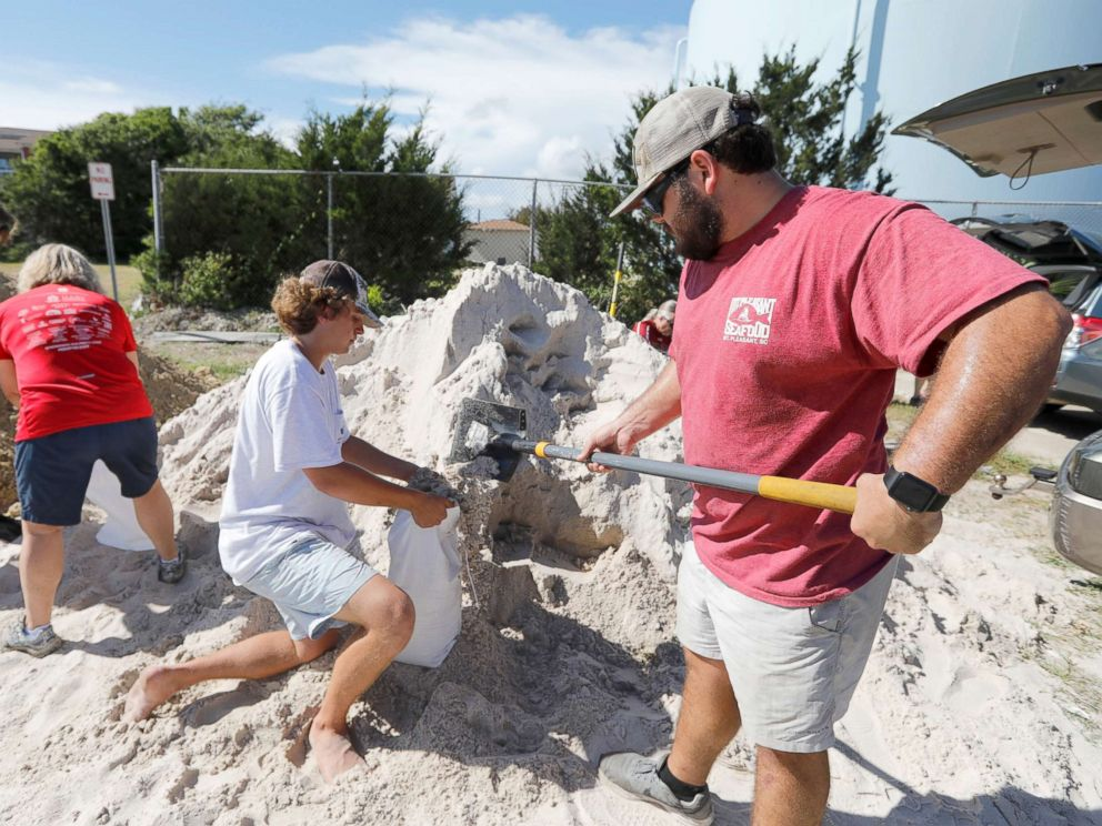 PHOTO: Walker Townsend, right, fills a sand bag while Dalton Trout, center, holds the bag at the Isle of Palms municipal lot where the city was giving away free sand in preparation for Hurricane Florence, Sept. 10, 2018.