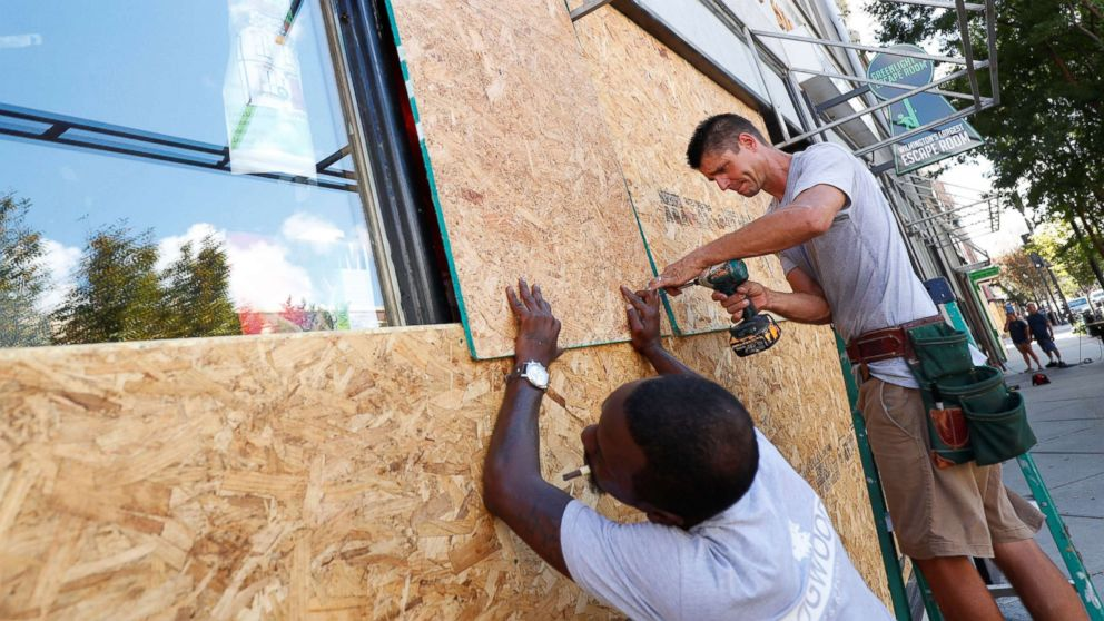 Workers are seen as they work to secure plywood ahead of the arrival of Hurricane Florence in Wilmington, North Carolina, Sept. 12, 2018.