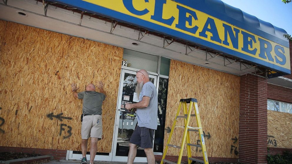 Michael Schwartz (L) and Jay Schwartz secure plywood over the windows of their business ahead of the arrival of Hurricane Florence, Sept. 11, 2018, in Myrtle Beach, S.C.