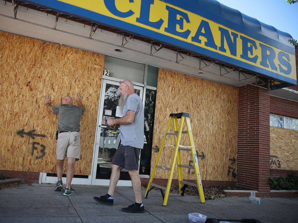 PHOTO: Michael Schwartz (L) and Jay Schwartz secure plywood over the windows of their business ahead of the arrival of Hurricane Florence, Sept. 11, 2018, in Myrtle Beach, S.C.