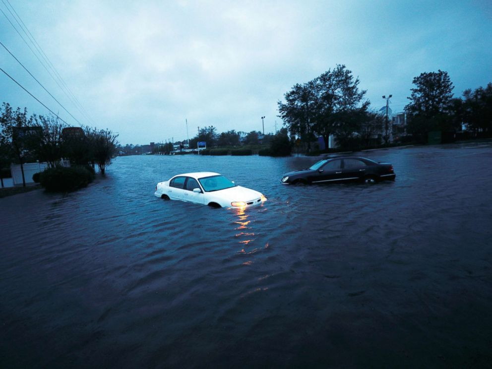 PHOTO: An abandoned cars hazard lights continue to flash as it sits submerged in rising flood waters during pre-dawn hours after Hurricane Florence struck in Wilmington, N.C., Sept. 15, 2018.