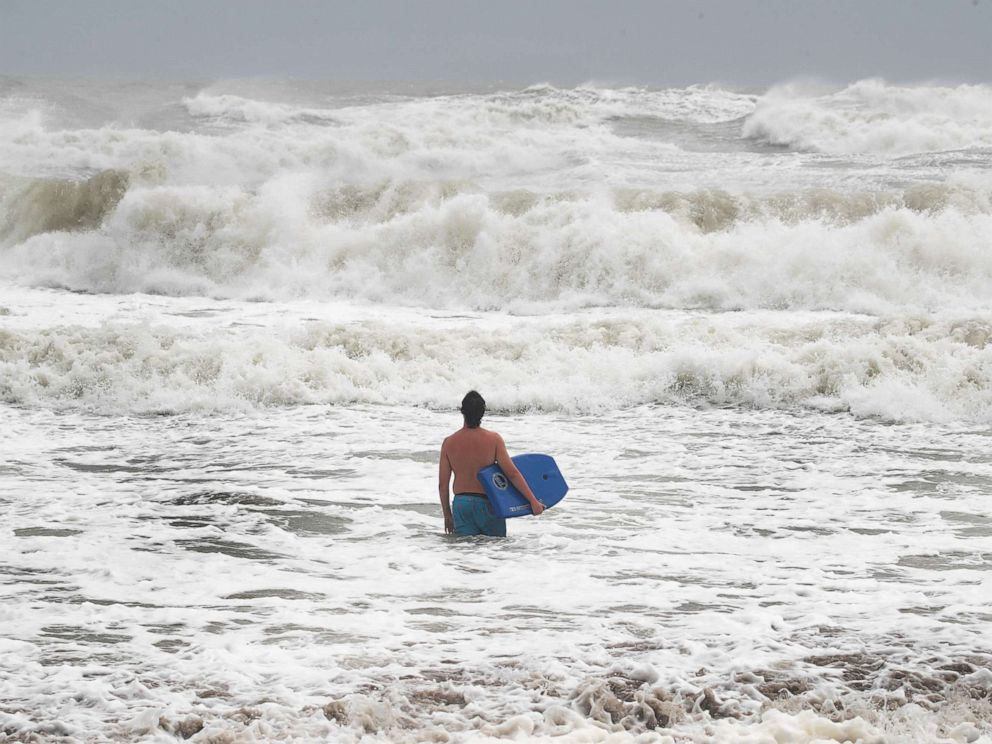 PHOTO: A swimmer takes advantage of big waves during high tide as Hurricane Dorian churns offshore on September 3, 2019, in Indialantic, Fla.