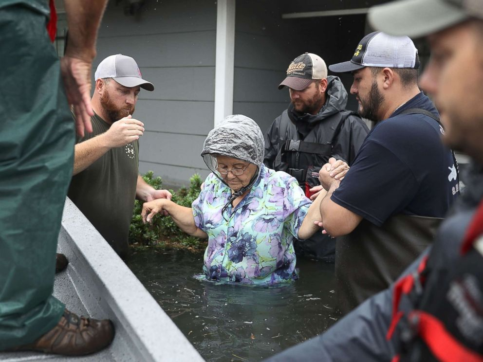 PHOTO: Volunteer rescuer workers help a woman from her home that was inundated with the flooding of Hurricane Harvey, Aug. 30, 2017 in Port Arthur, Texas.