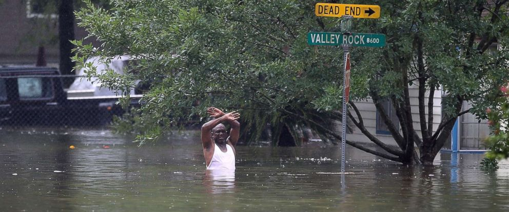PHOTO: A man waves down a rescue crew as he tries to leave the area after it was inundated with flooding from Hurricane Harvey, August 28, 2017, in Houston, Texas.