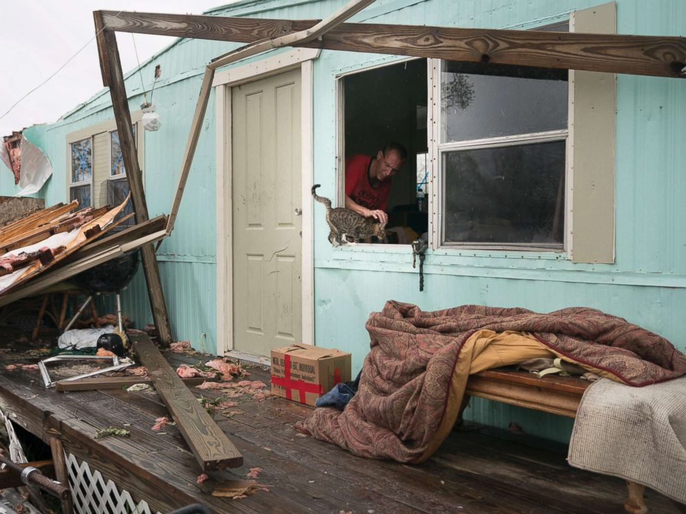 PHOTO: Sam Speights pauses to pet a kitten as he removes some possessions from his home in the aftermath of Hurricane Harvey in Rockport, Texas, Aug. 28, 2017.