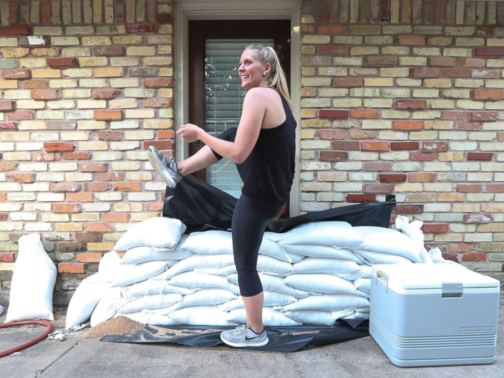 PHOTO: Lacey Williams exits the only door she can by stepping over sandbags that surround her home in Houston Aug. 24, 2017.