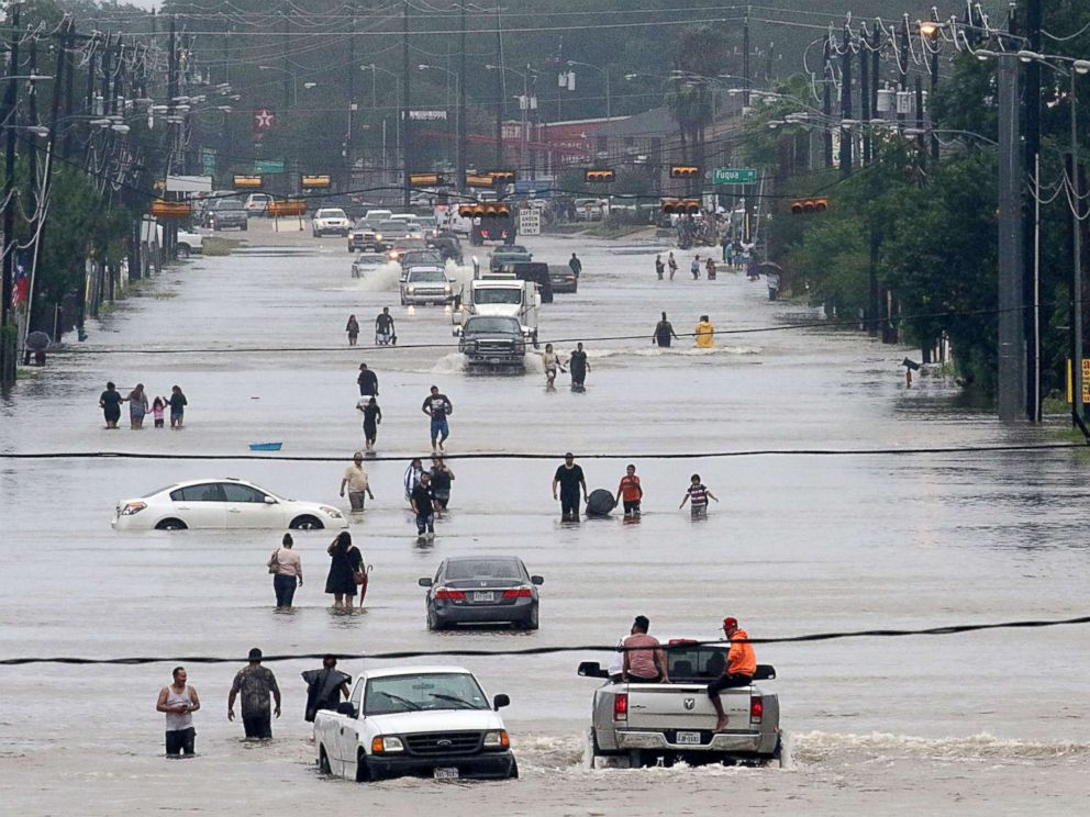 PHOTO: People walk through the flooded waters of Telephone Rd. in Houston on Aug. 27, 2017, as the city battles with tropical storm Harvey and resulting floods.