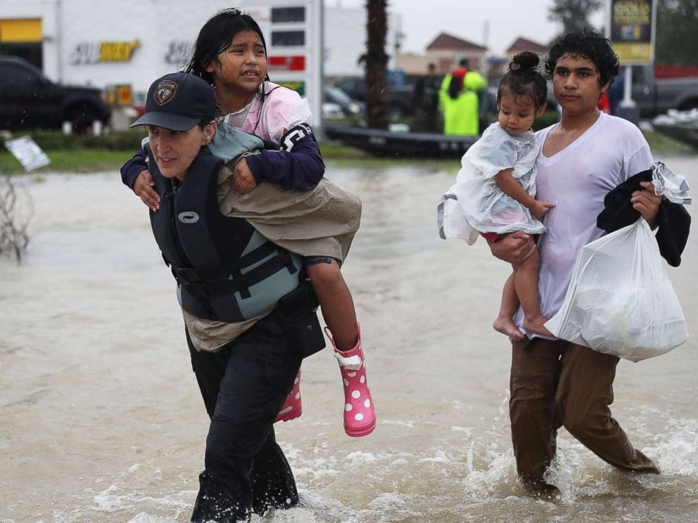 PHOTO: Evacuees are helped to dry land after their homes were inundated with flooding from Hurricane Harvey, Aug. 28, 2017 in Houston.