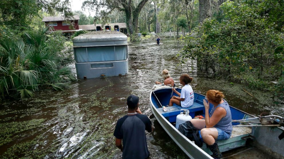 Family members ride in a small boat as Tony Holt's trailer is pulled out of the flood waters from Hurricane Irma in Gainesville, Florida, Sept. 14, 2017, after Hurricane Irma.