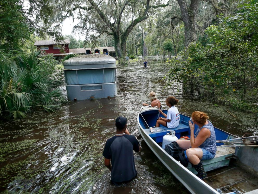 PHOTO: Family members ride in a small boat as Tony Holts trailer is pulled out of the flood waters from Hurricane Irma in Gainesville, Florida, Sept. 14, 2017, after Hurricane Irma.