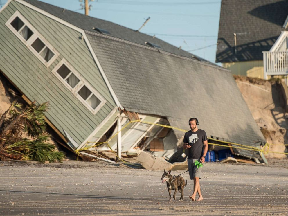 PHOTO: A man walks his dog by a beachfront home destroyed by Hurricane Irma in Vilano Beach, Fla, Sept. 13, 2017.