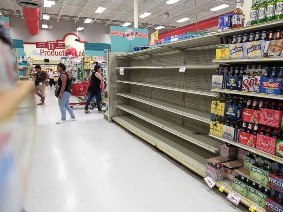 PHOTO: Customers walk near empty shelves that are normally filled with bottles of water after Puerto Rico Governor Ricardo Rossello declared a state of emergency in preparation for Hurricane Irma, in San Juan, Puerto Rico, Sept. 4, 2017.