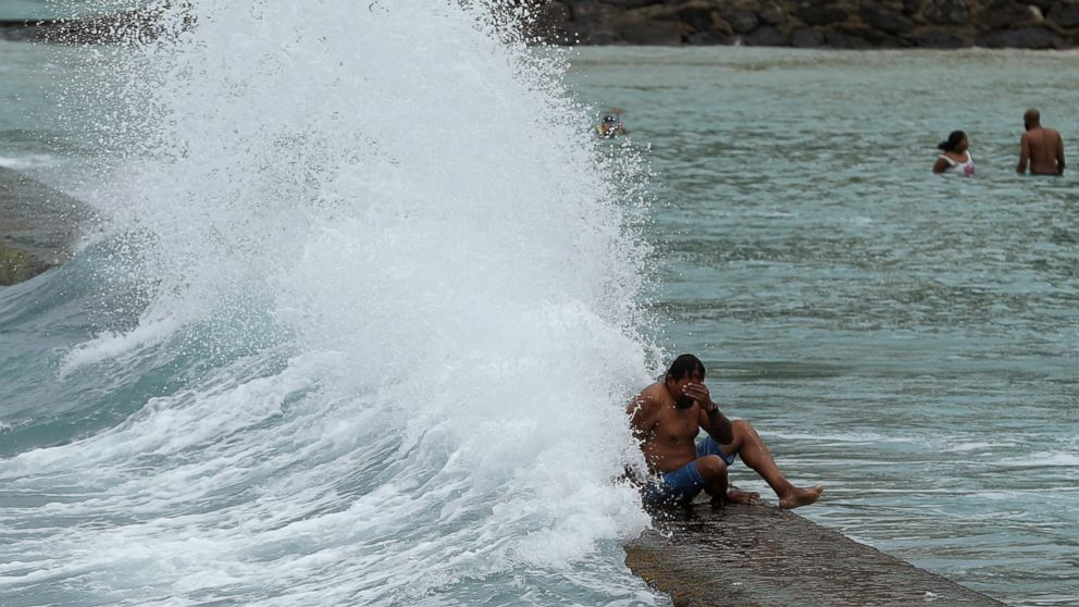 A large wave hits a man on a breakwater along Waikiki Beach ahead of Hurricane Lane, Friday, Aug. 24, 2018, in Honolulu. U.S. officials say a hurricane hitting Hawaii is likely to bring severe flooding and mudslides and they are preparing for the worst. (AP Photo/John Locher)