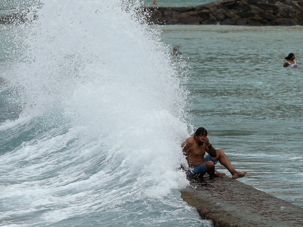 A large wave hits a man on a breakwater along Waikiki Beach ahead of Hurricane Lane, Friday, Aug. 24, 2018, in Honolulu.