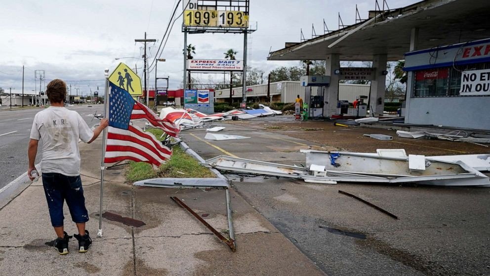 PHOTO: Dustin Amos walks near debris at a gas station in Lake Charles, La., Aug. 27, 2020.