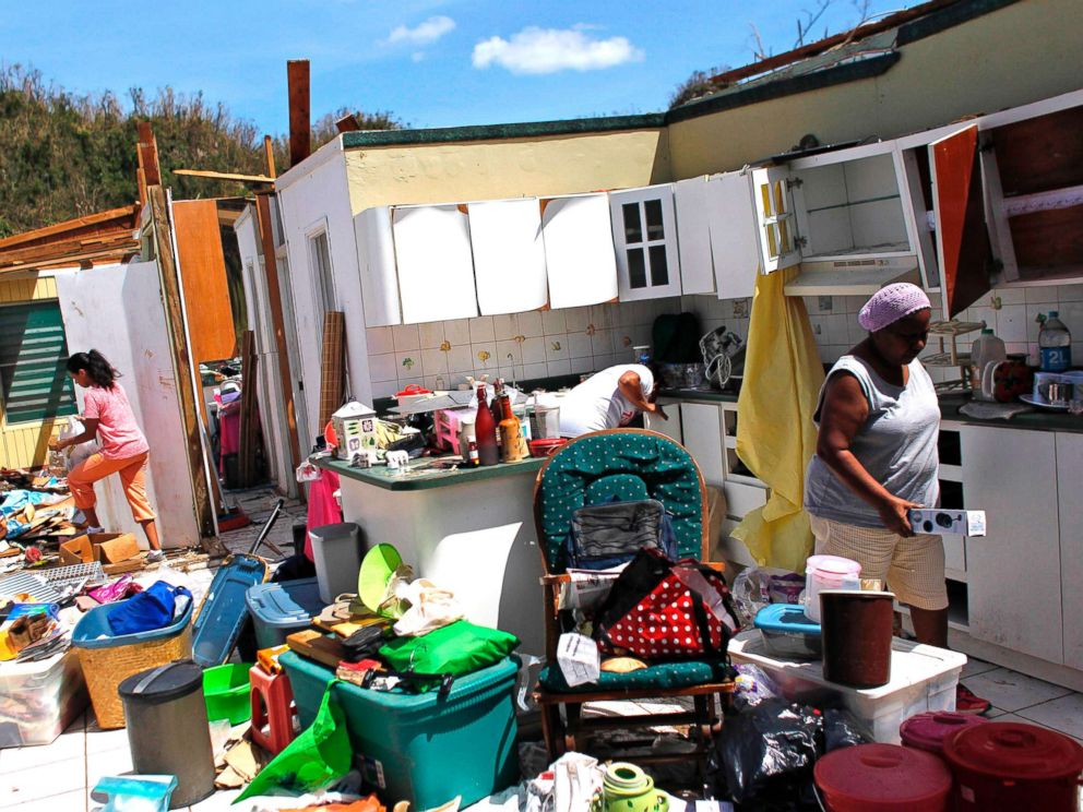 PHOTO: Family members collect their belongings after hurricane force winds destroyed their house in Toa Baja, west of San Juan, Puerto Rico, on Sept. 24, 2017.