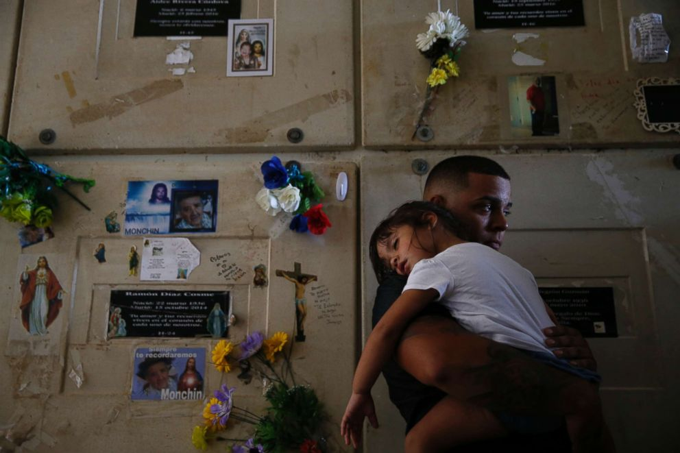 PHOTO: Orlando Gonzalez holds his daughter Nahielys as they attend the funeral of their neighbor Victor Ruiz Ramos in Corozal, Puerto Rico on Oct. 2, 2017.