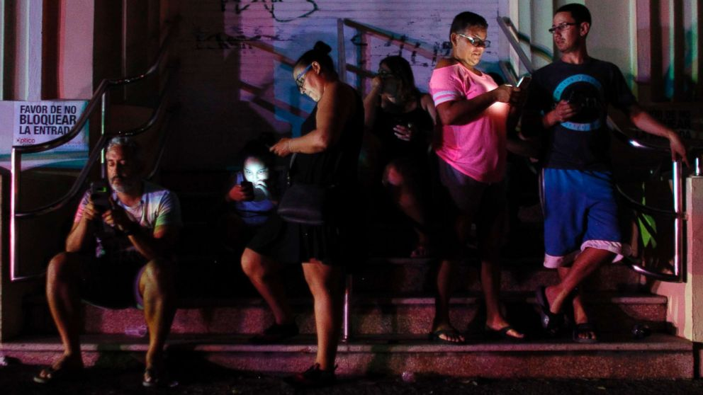 People use their cell phones at night in one of the few places with cell signal in San Juan, Puerto Rico, Sept. 25, 2017, where a 7pm-6am curfew has been imposed following impact of Hurricane Maria on the island.