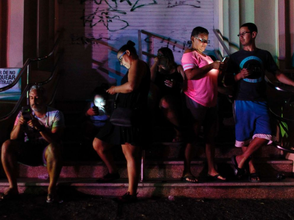 PHOTO: People use their cell phones at night in one of the few places with cell signal in San Juan, Puerto Rico, Sept. 25, 2017, where a 7pm-6am curfew has been imposed following impact of Hurricane Maria on the island.