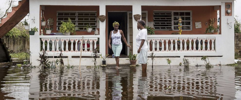 PHOTO: Residents wade through flood waters at their home days after Hurricane Maria made landfall, Sept. 22, 2017 in Loiza, Puerto Rico.