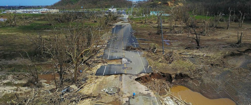PHOTO: A man rides his bicycle through a damaged road in Toa Alta, west of San Juan, Puerto Rico, Sept. 24, 2017, following the passage of Hurricane Maria.
