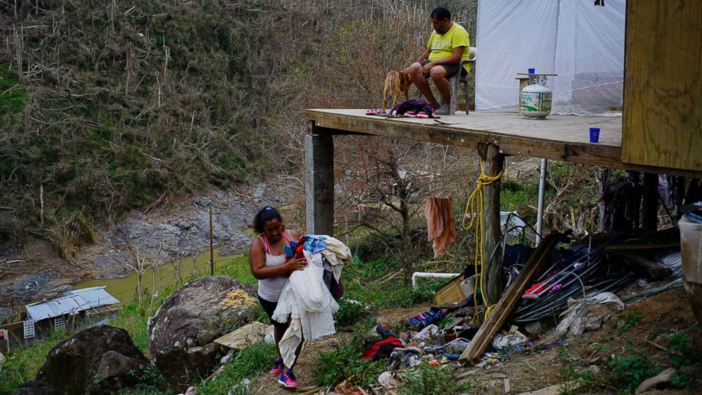 """Yadira Sortre and William Fontan Quintero clean their house, destroyed by Hurricane Maria in in Morovis, Puerto Rico, Oct. 1, 2017. """"We lost everything."""" Fontan said. They have three children, one lives in Chicago and two live with them in Puerto Rico."""