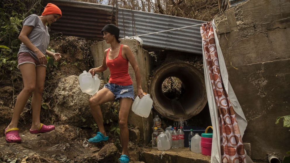 Yamilex Virella and her mother-in-law, Norma Andreu, carry water from a natural spring in the hill town of Toa Alta, Puerto Rico, Sept. 25, 2017.