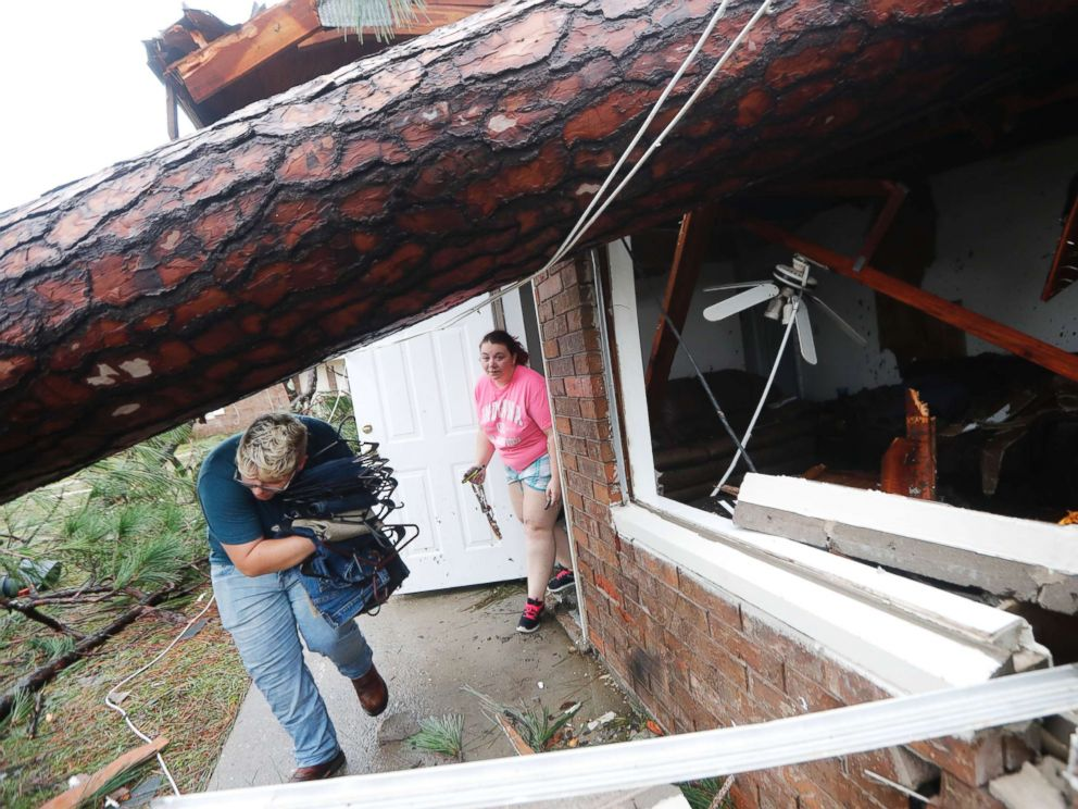PHOTO: People take belongings from their destroyed home after several trees fell on the house during Hurricane Michael in Panama City, Fla., Oct. 10, 2018.