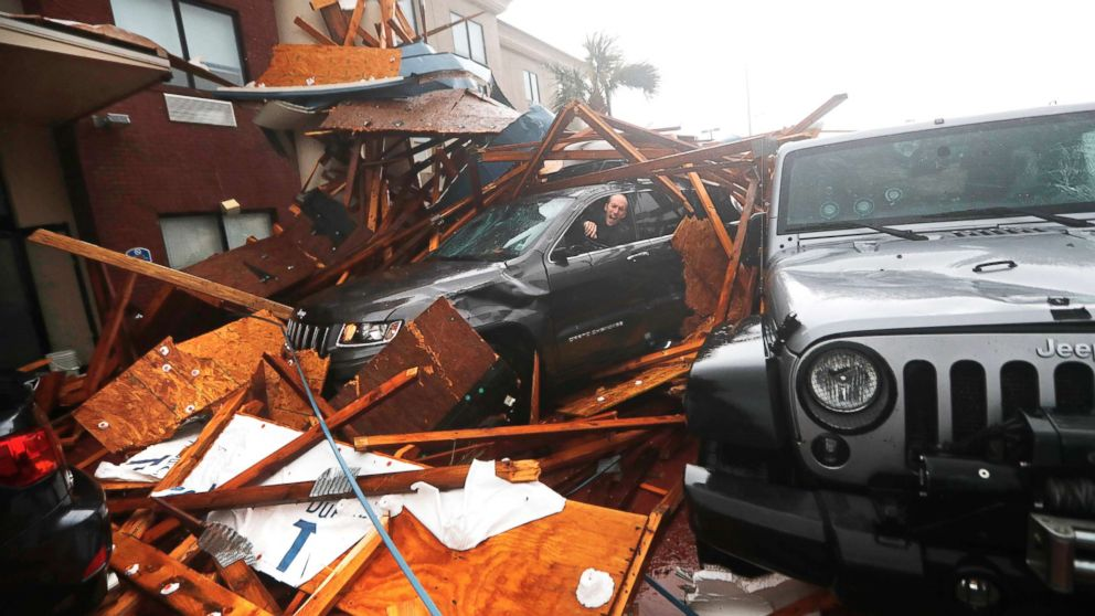 A storm chaser climbs into his vehicle during the eye of Hurricane Michael to retrieve equipment after a hotel canopy collapsed in Panama City Beach, Fla., Oct. 10, 2018.