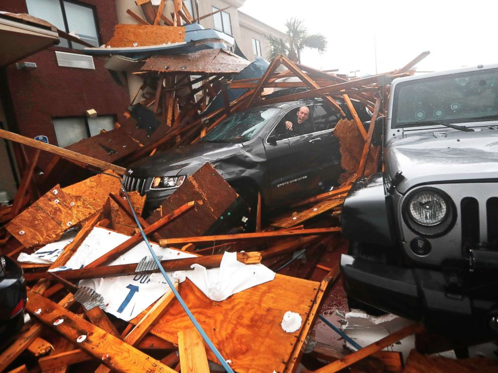 PHOTO: A storm chaser climbs into his vehicle during the eye of Hurricane Michael to retrieve equipment after a hotel canopy collapsed in Panama City Beach, Fla., Oct. 10, 2018.