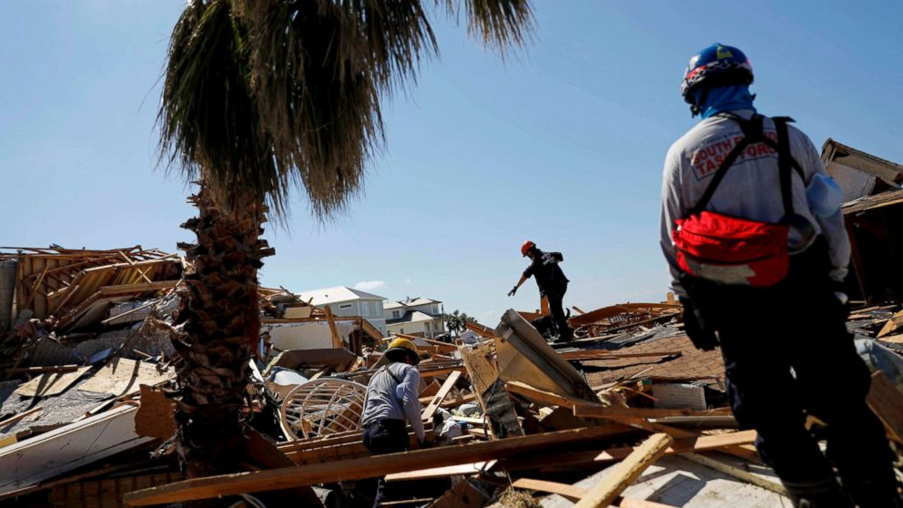 Members of a South Florida urban search and rescue team sift through a debris pile for survivors of Hurricane Michael in Mexico Beach, Fla., Oct. 14, 2018.