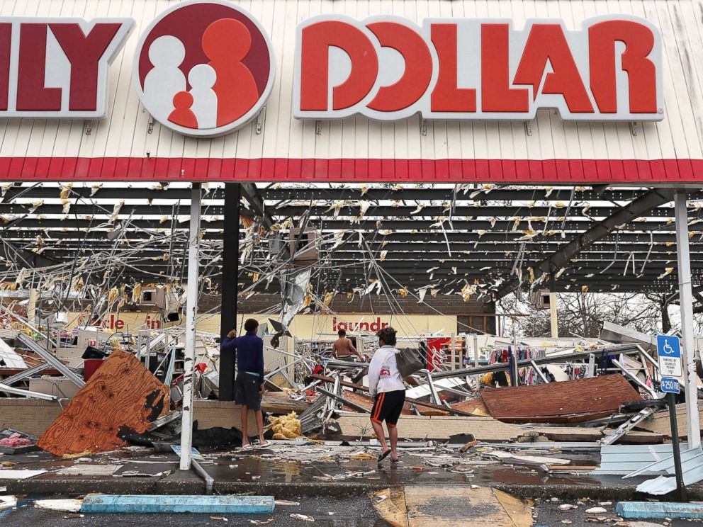 PHOTO: People look on at a damaged store after Hurricane Michael passed through on Oct. 10, 2018, in Panama City, Fla.