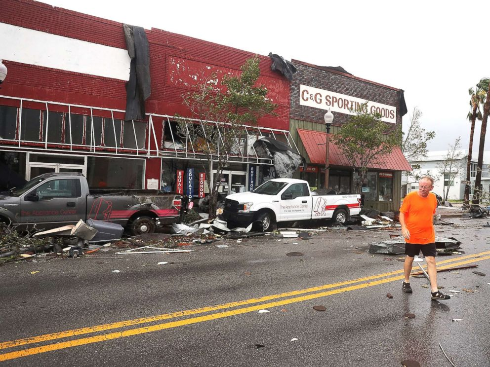 PHOTO: A man walks past damaged stores after hurricane Michael passed through the downtown area on Oct.10, 2018, in Panama City, Fla.