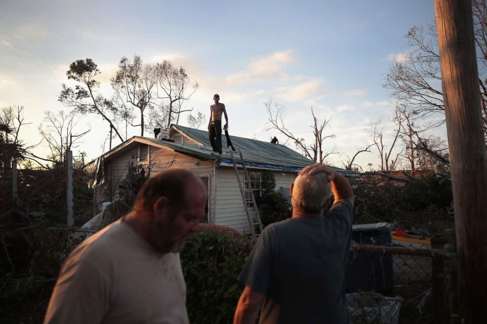 PHOTO: A man helps to tarp a roof on Oct. 18, 2018 in Panama City, Fla.