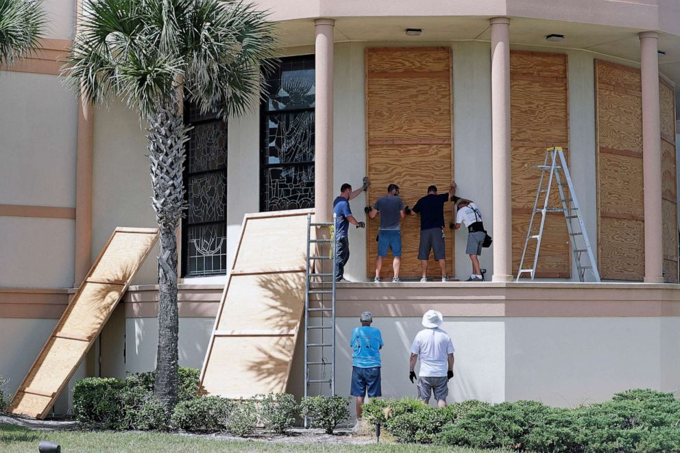 PHOTO: Workers cover stained glass windows with plywood sections at the Santa Maria del Mar Catholic Church in preparation for Hurricane Dorian, Aug. 30, 2019, in Flagler Beach, Fla.
