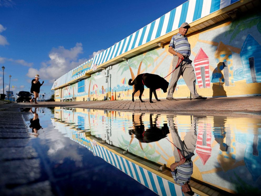 PHOTO: Beachgoers walk past a mural along the boardwalk as Hurricane Florence approaches the east coast in Atlantic Beach, N.C., Sept. 12, 2018.