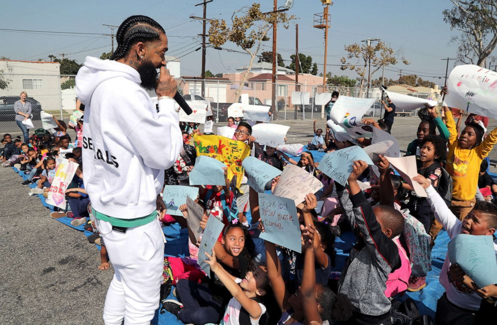 PHOTO: Rapper Nipsey Hussle speaks to kids after the opening of a basketball court, Oct. 22, 2018 in Los Angeles. Hussle partnered with Puma to refurbish the elementary school basketball court in south Los Angeles near where Nipsey grew up.