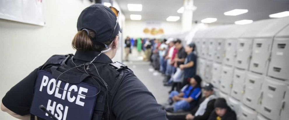 PHOTO: This image released by the US Immigration and Customs Enforcement (ICE) shows a Homeland Security Investigations (HSI) officer guarding suspected illegal aliens on August 7, 2019.