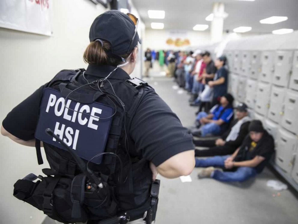 PHOTO: This image released by the US Immigration and Customs Enforcement on Aug. 7, 2019, shows a Homeland Security Investigations officer guarding suspected illegal aliens in Canton, Miss.