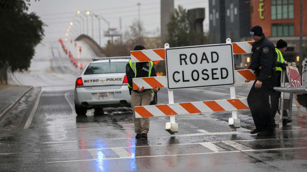 PHOTO: Two Savannah Chatham Metro Police officers set up a barricade in front of a bridge that was closed due to ice on the road, Jan. 3, 2018, in Savannah, Ga.