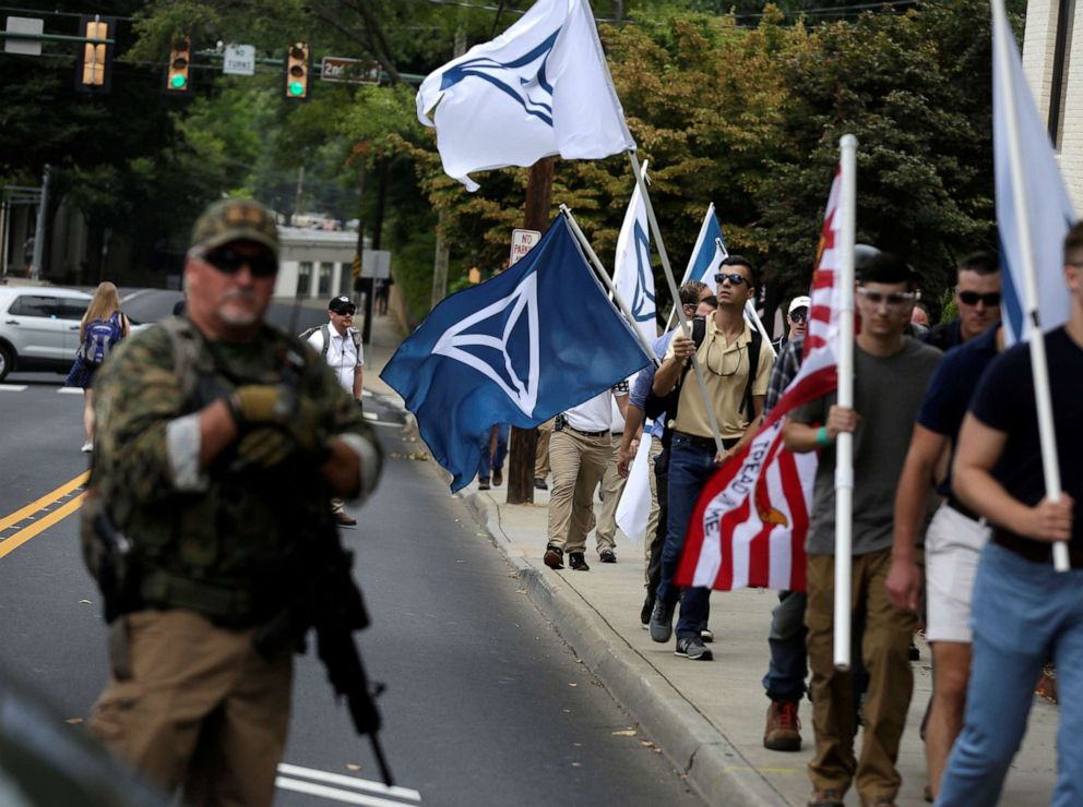 PHOTO: White nationalists carrying Identity Evropa flags pass a militia member as the they arrive for a rally in Charlottesville, Va., Aug. 12, 2017.