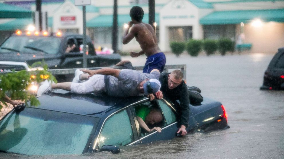 Mark Pickett, left, and Ryan Craig, right, work to rescue Bruce Salley, who was trapped in his car by flood waters in a supermarket parking in Rockford, Ill., June 18, 2018.
