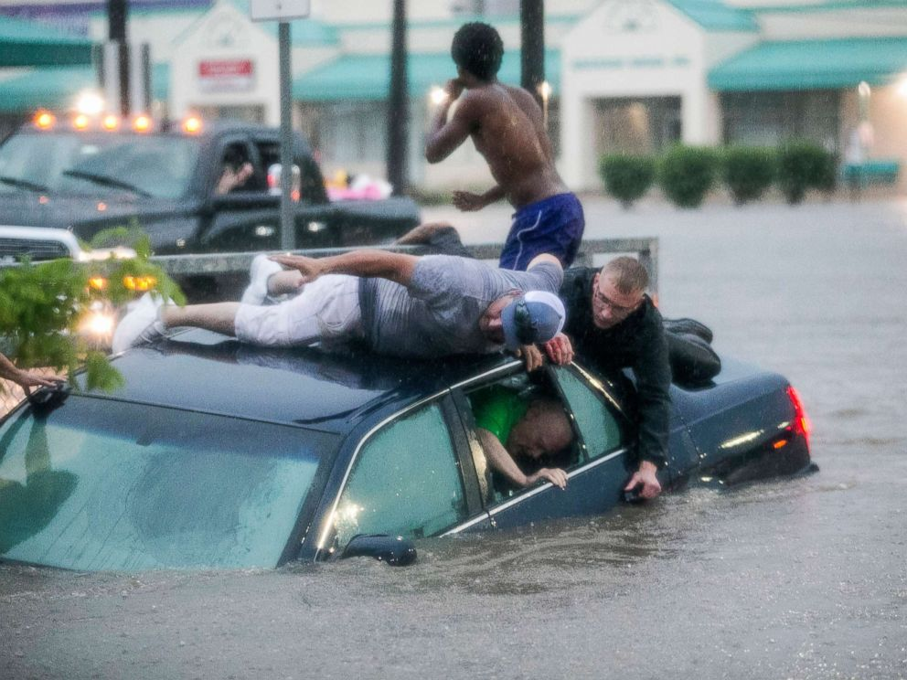 PHOTO: Mark Pickett, left, and Ryan Craig, right, work to rescue Bruce Salley, who was trapped in his car by flood waters in a supermarket parking in Rockford, Ill., June 18, 2018.