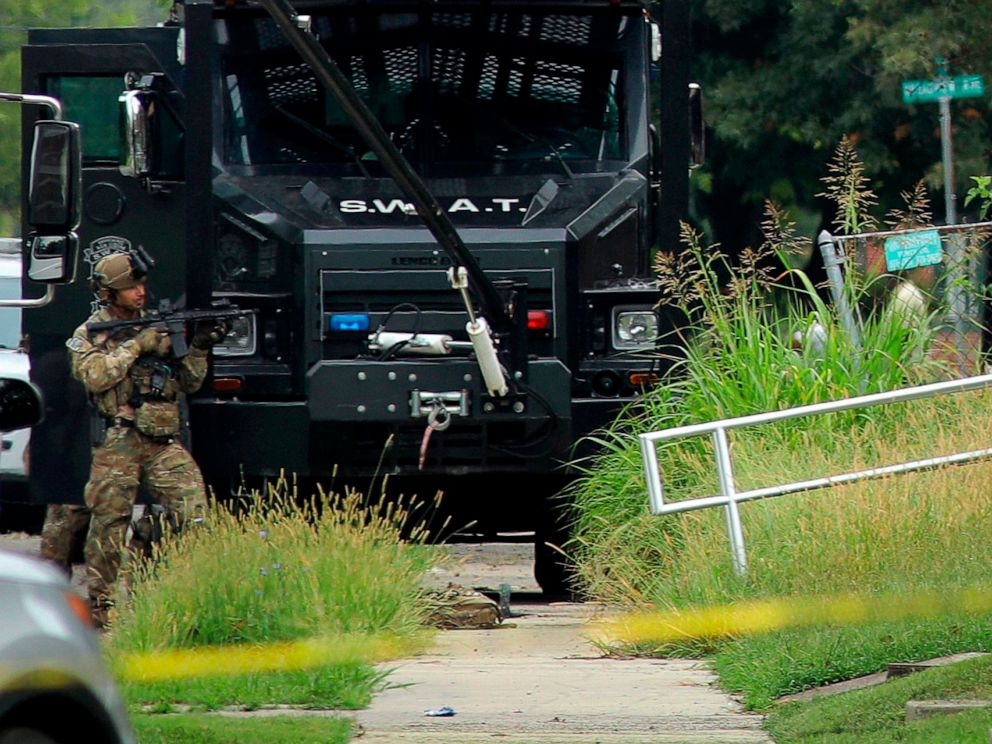 PHOTO: A police officer in tactical gear stands positioned near an Illinois State Police SWAT vehicle outside a building on 42nd Street near Van Buren Avenue, on Friday, Aug 23, 2019, in East St. Louis, Ill., after a trooper was shot serving a warrant.