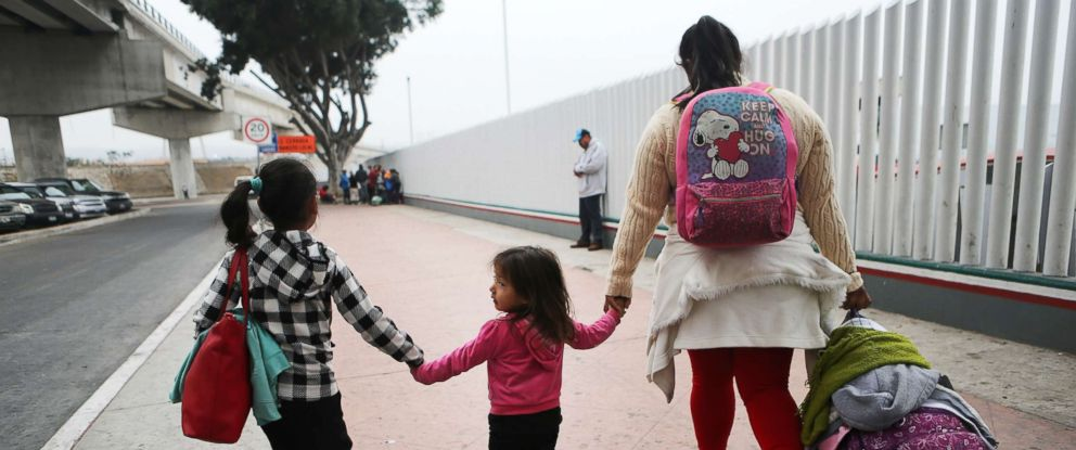 PHOTO: A migrant mother walks with her two daughters on their way to cross the port of entry into the U.S. for their asylum hearing on June 21, 2018 in Tijuana, Mexico.
