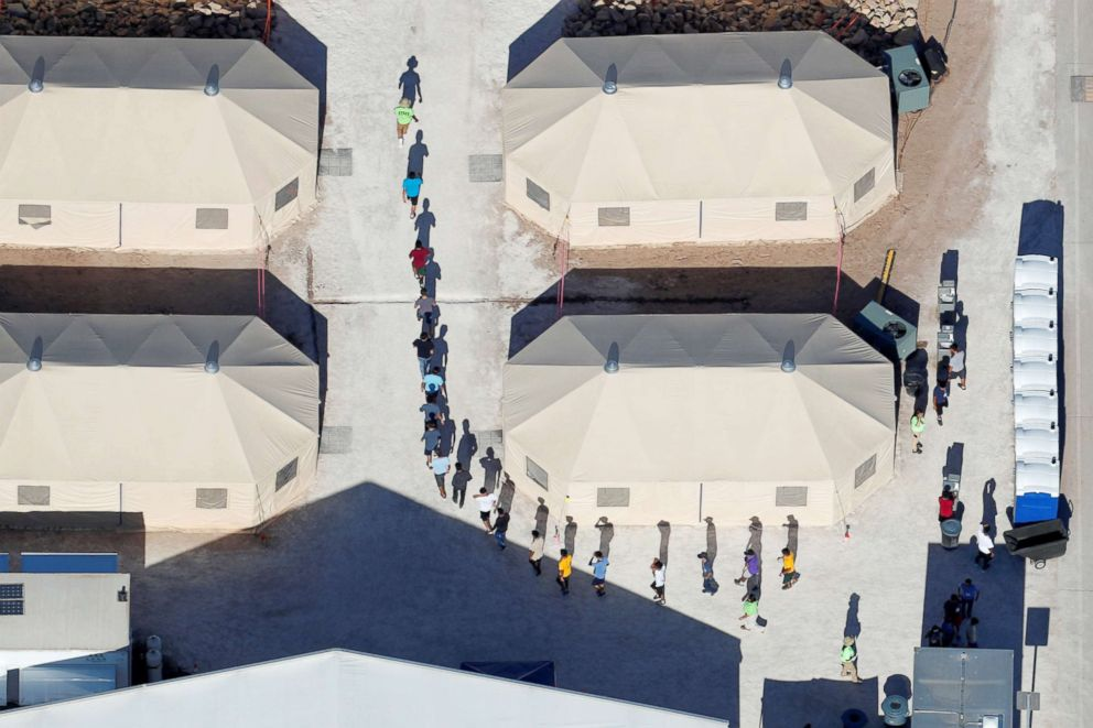 Immigrant children are shown walking in single file between tents in their compound next to the Mexican border in Tornillo, Texas, June 18, 2018.