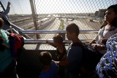 PHOTO: Migrant families from Mexico, fleeing from violence, wait to enter the United States to meet officers of the U.S. Customs and Border Protection to apply for asylum at Paso del Norte international border crossing bridge in Ciudad Juarez.