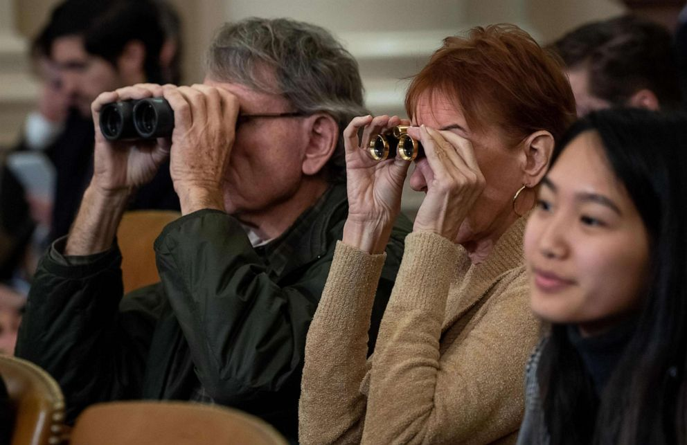 PHOTO: Members of the public use binoculars as they watch the House Judiciary Committee hearing on the impeachment of President Donald Trump on Capitol Hill in Washington, Dec. 4, 2019.