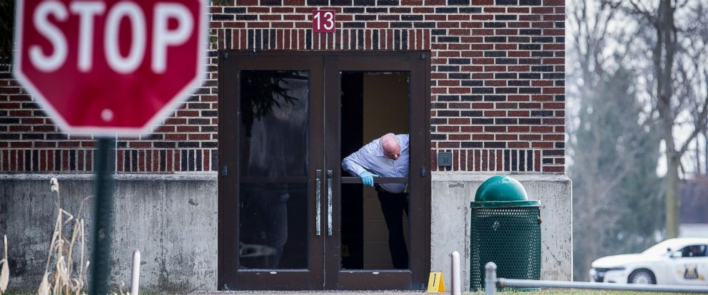 PHOTO: Investigators examine a shattered glass door at Dennis Intermediate School where police say an alleged school shooter made entrance the morning of Dec. 13, 2018.