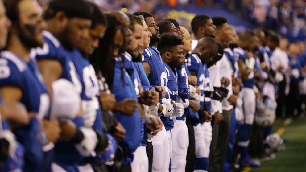 Members of the Indianapolis Colts lock arms during the playing of the national anthem before an NFL football game against the San Francisco 49ers, Oct. 8, 2017, in Indianapolis.